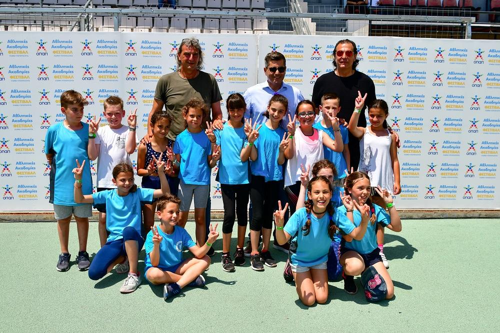 (από αριστερά) Γιάννης Καλιτζάκης, Οδυσσέας Χριστοφόρου, Επικεφαλής Εταιρικών και Ρυθμιστικών Υποθέσεων του ΟΠΑΠ, Τάσος Μητρόπουλος μαζί με παιδιά που συμμετείχαν στο φεστιβάλ