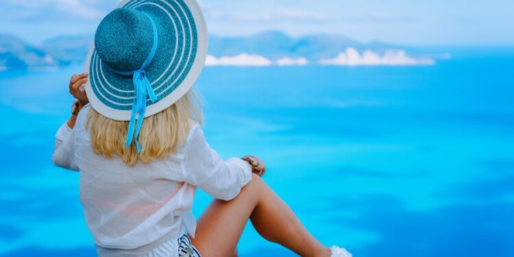 Attractive female tourist with turquoise sun hat enjoying amazing azure seascape, Greece. Cloudscape shadows on the sea surface in background.